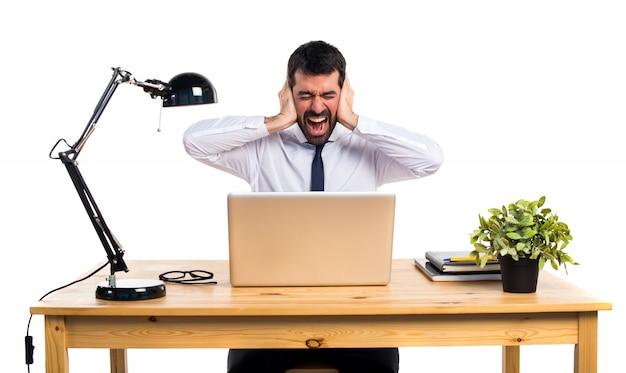 Homme d'affaires dans son bureau couvrant ses oreilles