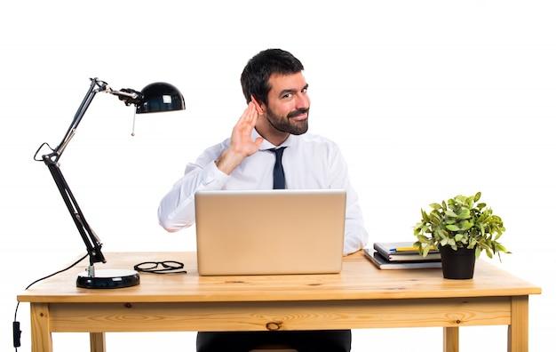 Homme d'affaires dans son bureau en écoutant quelque chose