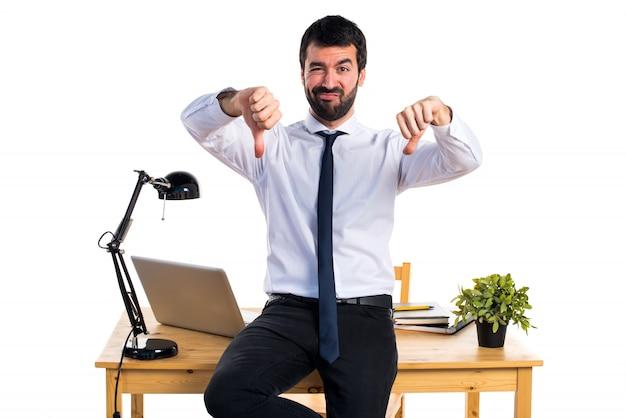 Homme d'affaires dans son bureau faisant un mauvais signal