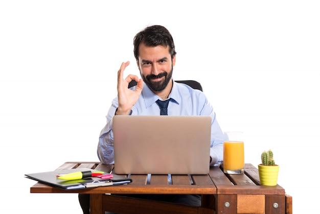 Homme d'affaires dans son bureau faisant signe ok