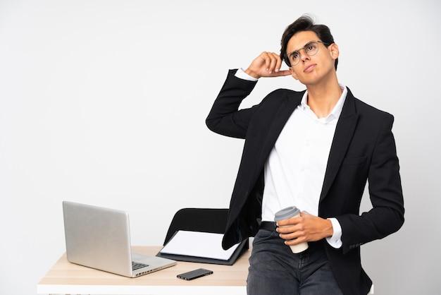 Homme d'affaires dans son bureau sur mur isolé mur blanc ayant des doutes et avec une expression de visage confuse