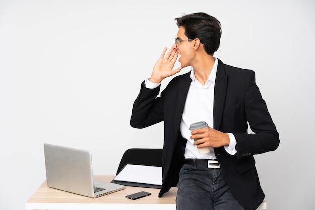 Homme d'affaires dans son bureau sur mur isolé mur blanc criant avec la bouche grande ouverte