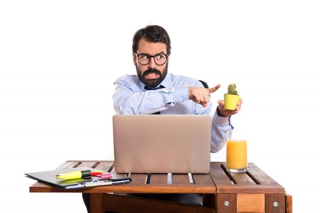 Homme D'affaires Dans Son Bureau Tenant Des Cactus Photo gratuit