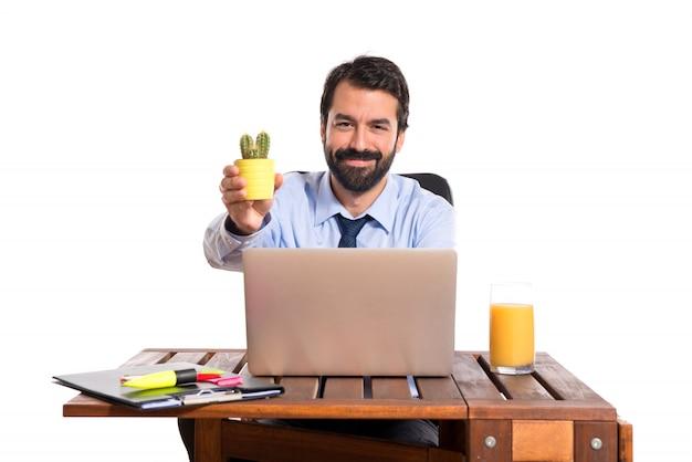 Homme d'affaires dans son bureau tenant des cactus