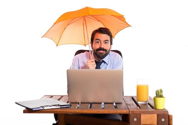 Homme d'affaires dans son bureau tenant un parapluie