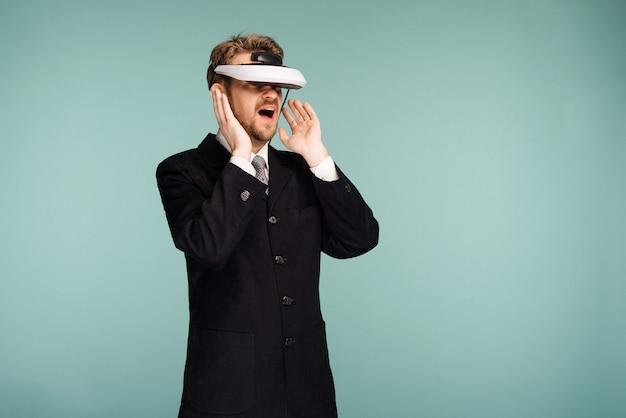 Homme d'affaires dans une tenue formelle portant des lunettes de réalité virtuelle a ouvert la bouche de surprise