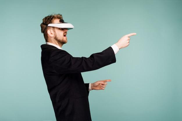 Homme d'affaires dans une tenue formelle portant des lunettes de réalité virtuelle pointant du doigt