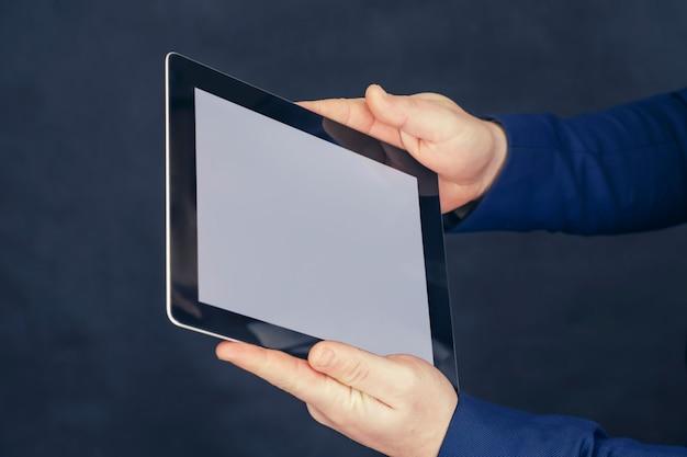 Homme d'affaires dans une veste bleue est titulaire d'une maquette d'une tablette avec un écran blanc