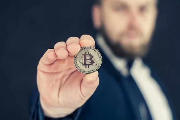 Un homme d'affaires dans une veste bleue tenant bitcoin dans ses mains. monnaie virtuelle et concept de blockchain.