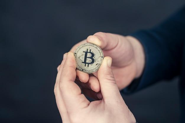Un homme d'affaires dans une veste bleue tenant bitcoin dans ses mains.