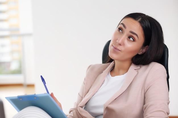 Homme d'affaires dans une veste rose assis sur une chaise à prendre des notes dans un cahier