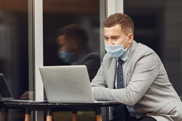 Homme d'affaires dans une ville. personne dans un masque. guy avec ordinateur portable.