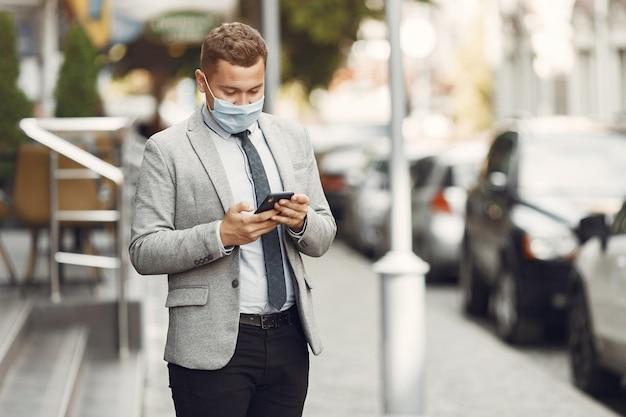 Homme d'affaires dans une ville. personne dans un masque. guy avec téléphone.