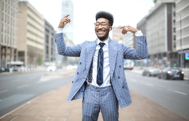 Homme d'affaires danser dans la rue tout en écoutant de la musique avec des écouteurs