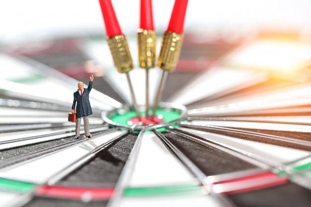 Homme d'affaires, debout sur le centre cible du jeu de fléchettes avec idée de flèches de l'objectif financier et commercial
