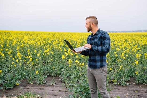 Homme d & # 39; affaires debout dans le champ de colza avec ordinateur portable