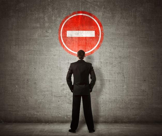 Homme d'affaires debout devant le panneau d'interdiction d'entrée