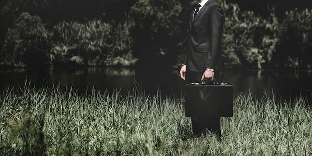 Homme affaires, debout, herbe, dehors