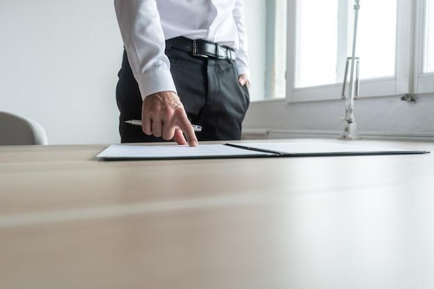 Homme d'affaires debout à son bureau pointant vers un document dans un dossier où signer.