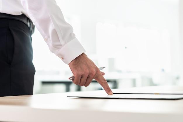 Homme d'affaires debout à son bureau pointant vers un document, une demande ou un contrat tenant un stylo.