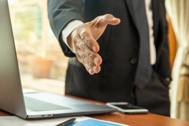 Homme d'affaires debout et tendre la main pour trembler.