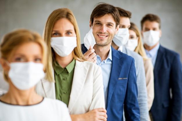 Homme d'affaires décollant son masque facial de protection et regardant la caméra avec les membres de l'histeam debout dans la ligne au bureau