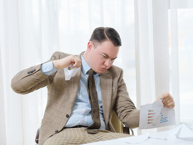 Homme d'affaires déçu en colère déchirant des documents en morceaux.