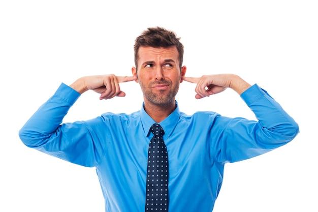 Homme d'affaires de dégoût avec les doigts dans les oreilles