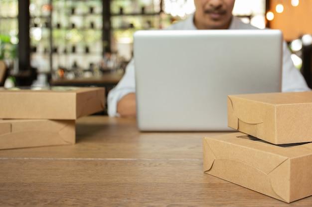 Homme d'affaires de démarrage travaillant sur ordinateur portable avec colis sur la table.