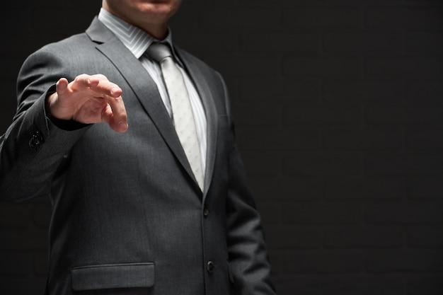 Homme d'affaires démontrant quelque chose dans ses doigts, habillé en costume gris, fond de mur sombre