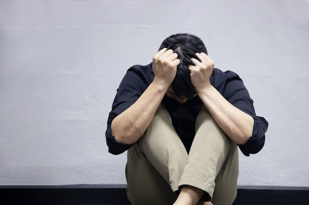 L'homme d'affaires de dépression assis près du mur sur le sol