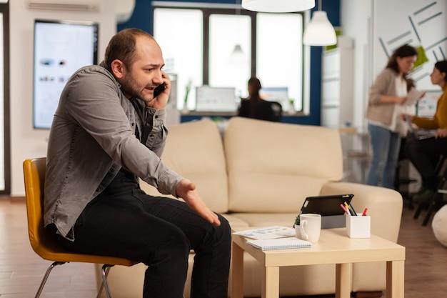 Un homme d'affaires désespéré et frustré se dispute avec une autre personne dans une entreprise en démarrage lors d'un appel téléphonique