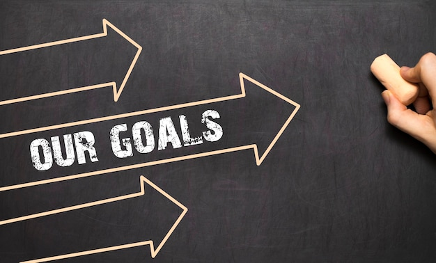 Un homme d'affaires dessine le concept de nos objectifs avec des flèches sur le tableau noir