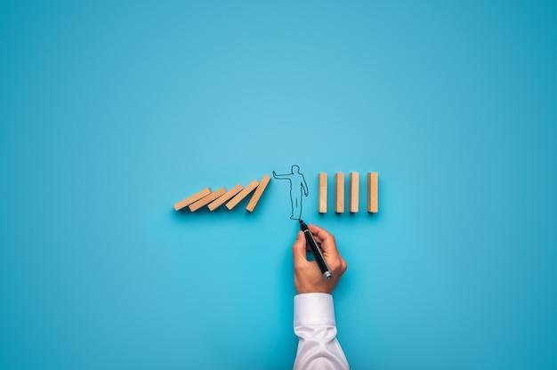 Homme d'affaires dessiné à la main, arrêtant la chute des dominos