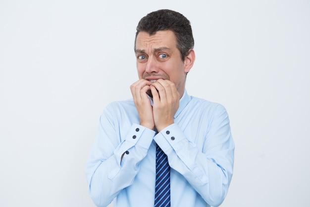Un homme d'affaires détaché mâchant les ongles