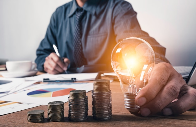 Homme d'affaires détenant une ampoule avec de l'argent en pièces et copie espace pour la comptabilité, les idées et le concept créatif.