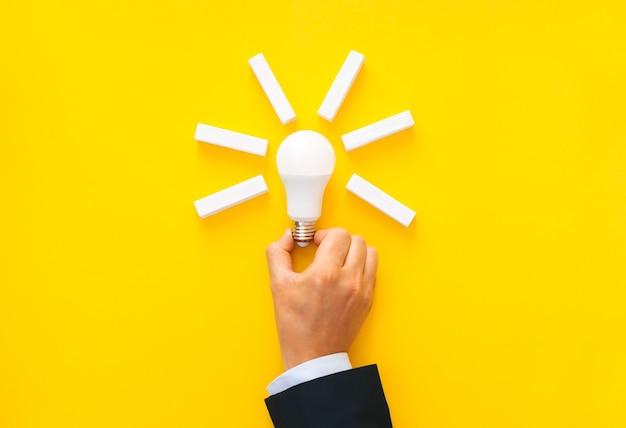 Homme d'affaires détenant une ampoule avec des blocs en bois avec espace de copie. objectifs de création d'entreprise