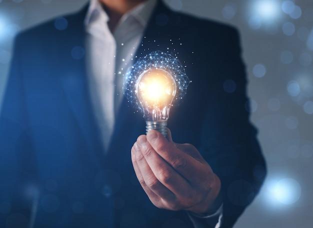 Homme d'affaires détenant une ampoule futuriste avec des idées et une technologie innovante.