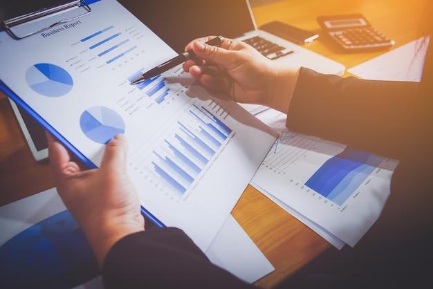 Homme d'affaires détenant et analyse des graphiques d'investissement travaillant au bureau. concept de travail d'entreprise.