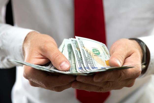 Homme d'affaires détenant de l'argent dans ses mains. un homme tenant des dollars américains