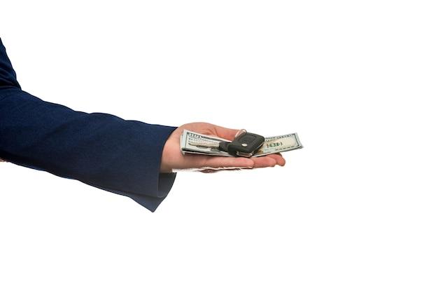 Homme d'affaires détenant des billets d'un dollar et des clés de voiture isolés sur gros plan de mur blanc. acheter ou louer un concept de voiture
