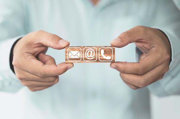 Homme d'affaires détenant un bloc de bois qui imprime le contact commercial d'écran comprend l'adresse e-mail et le numéro de téléphone