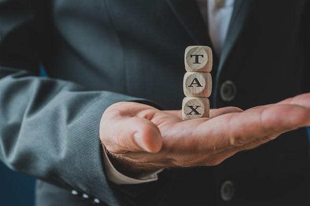 Homme d'affaires détenant des dés en bois empilés la taxe d'orthographe dans sa paume.