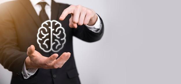 Homme d'affaires détenant un cerveau abstrait et une icône de marketing numérique, de stratégie et d'objectif commercial d'investissement de croissance, de médias et de technologie.