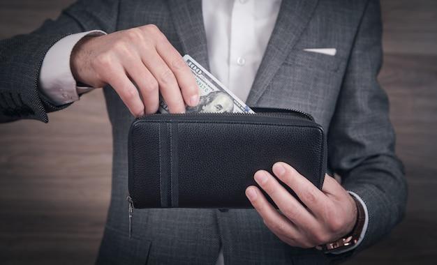 Homme d'affaires détenant des dollars avec portefeuille.