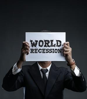 Homme d'affaires détenant du papier couvrant son visage avec le texte de la récession mondiale