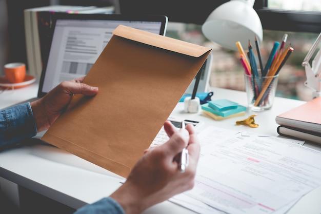 Homme d'affaires détenant l'enveloppe du document sur le bureau information table.business.
