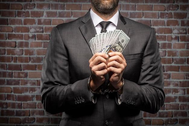 Homme d'affaires détenant des factures d'argent avec des menottes dans une prison. concept de corruption, politiciens corrompus, entreprises illégales. fond de brique.