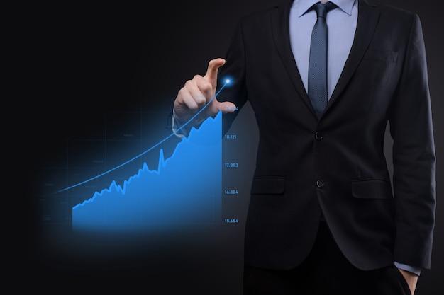 L'homme d'affaires détenant des graphiques holographiques et des statistiques boursières gagne des bénéfices. concept de planification de la croissance et de stratégie d'entreprise. affichage d'un écran numérique de bonne forme économique.