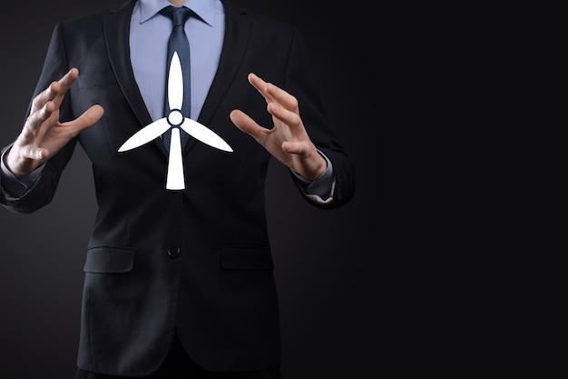 Homme d'affaires détenant une icône d'un moulin à vent qui produit de l'énergie environnementale. fond sombre.